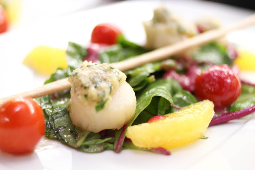 Jakobsmuscheln auf einen Salat serviert